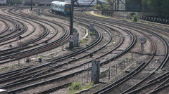 Electric commuter train rounds a curve to enter Victoria station London Stock Footage