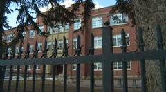 Dolly shot, old high school behind wrought iron fence, big trees Stock Footage