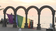 Gay pride flag being hung from the arches down town in Puerto Vallarta, beach Stock Footage