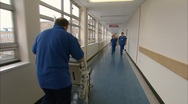 Orderly wheeling patient down corridor Stock Footage