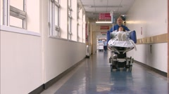 Orderly wheeling patient down corridor - stock footage