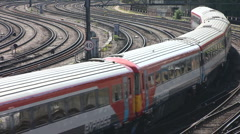 Electric express and commuter trains rounds a curve to leave London - stock footage