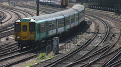 Electric commuter train and an express train round a curve to enter London Stock Footage