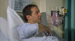 Nurse talking to patient in hospital bed - stock footage