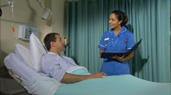 Nurse talking to patient in hospital bed Stock Footage