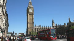 Crowds of people cross the road below Big Ben in London England Stock Footage