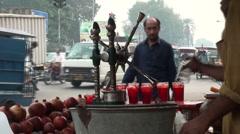 Selling fresh juice on busy Pakistan road Stock Footage