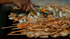 Grilling chicken on a stick and fresh vegetables at the fair Stock Footage
