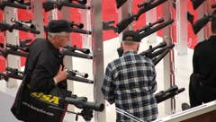 Gentlemen checking out scopes at gunshow(HD)c Stock Footage
