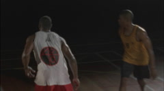 Three men play basketball on an indoor court. Stock Footage