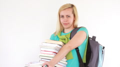 Young female student holding heavy big stack of books, isolated HD Stock Footage