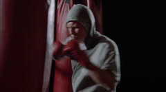 A boxer practices by hitting punching bags. Stock Footage