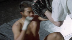 A boxer practices punching with the help of another person wearing a glove. Stock Footage