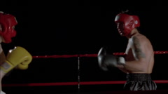 Two boxers fight in a boxing ring. - stock footage