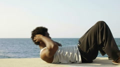 Black man exercising abs near the sea Stock Footage