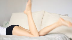 Buttocks and legs of slim woman lying on bed Stock Footage