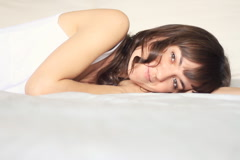 Young beautiful happy woman lying in bed - stock footage