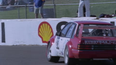 A racing car drives around a track as people watch. Stock Footage