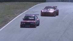 Two cars race down a track and prepare to go into a sharp turn. Stock Footage