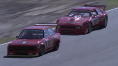 Two race cars enter a hard turn. Stock Footage
