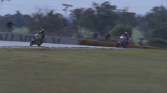 Motorcyclists race around a track, spectators watch. Stock Footage