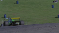 A racing car races by as people sit on the grass. Stock Footage