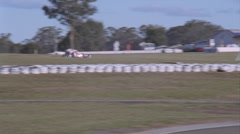 Two race cars head down a straight away on a track. Stock Footage