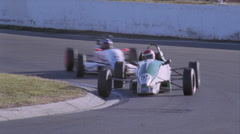 Two racing cars round a bend in the racetrack. Stock Footage