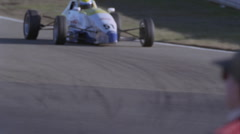 A race car begins to enter into a turn on a race track. Stock Footage