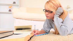 Young blond-haired woman studying Stock Footage
