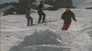 Three people are skiing, one jumps over a mound of snow. Stock Footage