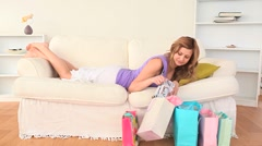 Blond-haired woman lying on the sofa looking at her shopping Stock Footage