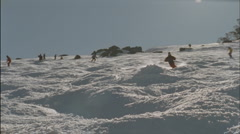 Skier jumping from the edge of a snow ridge. Stock Footage