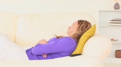 Blond-haired woman taking a nap then answering the phone Stock Footage