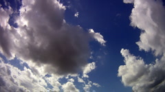 Fisheye view of clouds clearing to reveal the sun against a blue sky Stock Footage