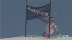 A competitive skier skis down a hill and snowflakes fly. Stock Footage
