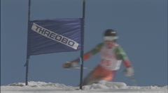 A skier moves swiftly down hill through a slalom course. Stock Footage