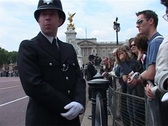 Stock Video Footage of Policeman and Crowds at Buckingham Palace, London England