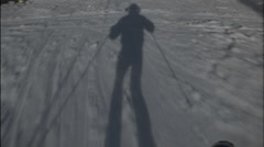 A skier's shadow precedes him down the hill. Stock Footage