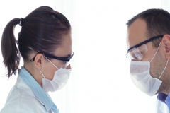 Profiles of male and female scientist looking at test tube with yellow liquid Stock Footage
