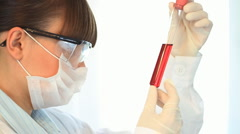 Female scientist examines test tube with red liquid, steadicam shot Stock Footage