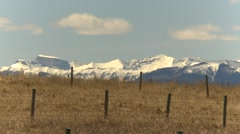 Snowy mountains in early spring fenced pasture, heat shimmers, #1 Stock Footage