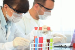 Female scientist examines test tube with yellow liquid Stock Footage