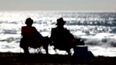 Beach bums 03 - silhouette rack focus Stock Footage