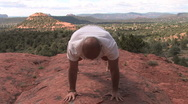 Man Does Yoga Pose in Red Rocks Stock Footage