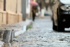 Car driving on rainy cobblestones street Stock Footage