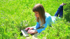Beautiful lady lying in the grass beside the laptop. Dolly in Stock Footage