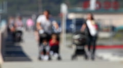 Beach family 04 - family walking with strollers - out of focus Stock Footage