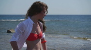 Stock Video Footage of HD1080 Young girl in Bikini looking at the ocean turns toward camera