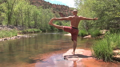 Man Does One Leg Yoga Stand At Creek- back view Stock Footage